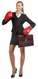 Businesswoman wearing boxing gloves holding Royalty Free Stock Photography