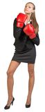 Businesswoman wearing boxing gloves, looking ahead Royalty Free Stock Photography