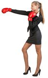 Businesswoman wearing boxing gloves punching Royalty Free Stock Photography