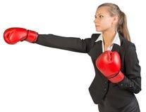 Businesswoman wearing boxing gloves punching Stock Photos