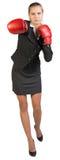 Businesswoman wearing boxing gloves punching Royalty Free Stock Image