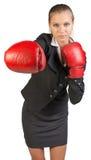 Businesswoman wearing boxing gloves punching Royalty Free Stock Photos