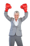 Businesswoman wearing boxing gloves and raising her arms Royalty Free Stock Images
