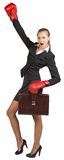 Businesswoman wearing boxing gloves wins Stock Photos