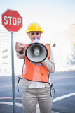 Businesswoman wearing builders clothes screaming in megaphone Stock Photos