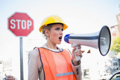 Businesswoman wearing builders clothes shouting in megaphone Royalty Free Stock Photos
