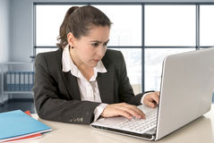 Businesswoman wearing business suit working on laptop computer at modern office room Stock Photos