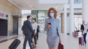 Businesswoman wearing face mask and checking her phone at airport