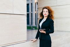 Businesswoman wearing formal clothes, holding modern gadget which she uses for reading messages, e-mails or information. Young fem. Ale communicating with her stock images