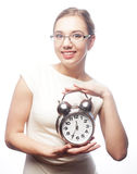 Businesswoman wearing glasses holding alarm clock Stock Photo