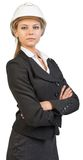 Businesswoman wearing hard hat, her arms crossed Stock Photo