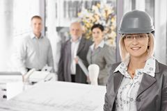 Businesswoman wearing hardhat in office. Businesswoman wearing hardhat in architectural office, team standing in background Royalty Free Stock Images