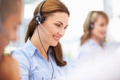 Businesswoman wearing headset. Businesswomen wearing headset smiling at work Royalty Free Stock Images