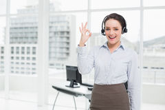 Businesswoman wearing headset while gesturing ok sign in the office Stock Photos