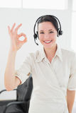 Businesswoman wearing headset while gesturing ok sign in office Royalty Free Stock Photography