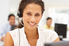 Businesswoman wearing headset in office. Businesswomen wearing headset in office smiling to camera Royalty Free Stock Photo