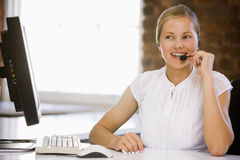 Businesswoman wearing headset in office smiling Royalty Free Stock Photography