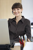 Businesswoman Wearing Headset Sitting At Desk Royalty Free Stock Photo