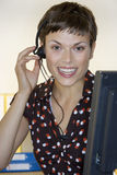 Businesswoman wearing telephone headset, sitting at desk, smiling, front view, close-up Royalty Free Stock Photography
