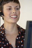 Businesswoman wearing telephone headset, smiling, close-up Royalty Free Stock Images