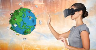 Businesswoman wearing VR glasses by low poly earth royalty free stock image