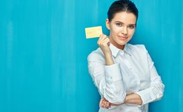 Businesswoman wearing white shirt holding credit card. Blue wall background royalty free stock photo