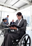 Businesswoman in a wheelchair reading a report Stock Image