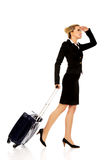 Businesswoman with wheeled suitcase covering eyes with hand Stock Image