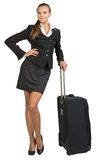 Businesswoman with wheeled travel bag, hand on hip Stock Images