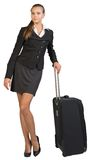 Businesswoman with wheeled travel bag, looking at Royalty Free Stock Images