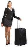 Businesswoman with wheeled travel bag, looking at Stock Photo
