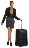 Businesswoman with wheeled travel bag makes step Stock Images
