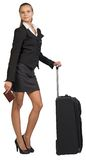 Businesswoman with wheeled travel bag and passport Stock Photo