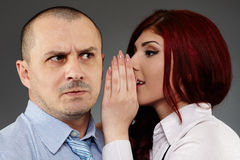 Businesswoman whispering in her boss' ear Stock Photos