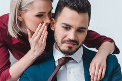 businesswoman whispering something to handsome young businessman royalty free stock image