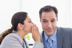 Businesswoman whispering something to her colleague Royalty Free Stock Image