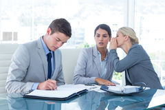 Businesswoman whispering something to her colleague Royalty Free Stock Images
