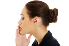 Businesswoman whispering to someone. Stock Photo