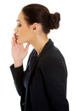 Businesswoman whispering to someone. Stock Image