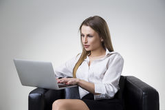 Businesswoman in a white blouse sitting in a leather armchair with her laptop. Stock Photo