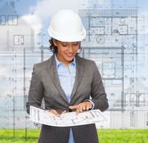 Businesswoman in white helmet with blueprint Stock Image
