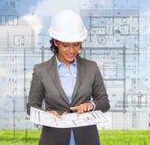 Businesswoman in white helmet with blueprint Stock Image