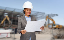 Businesswoman in white helmet with blueprint Royalty Free Stock Photography
