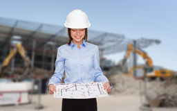 Businesswoman in white helmet with blueprint Stock Photos