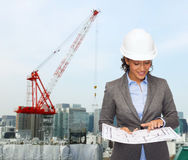 Businesswoman in white helmet with blueprint Stock Photo