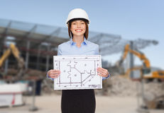 Businesswoman in white helmet with blueprint Royalty Free Stock Images