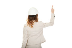 Businesswoman in white helmet pointing up. Stock Photos