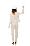 Businesswoman in white helmet pointing up. Royalty Free Stock Image