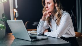 Businesswoman in white shirt is sitting in office at table in front of computer and pensively looks at screen of laptop Stock Photography