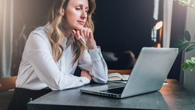 Businesswoman in white shirt is sitting in office at table in front of computer and pensively looks at screen of laptop Stock Photo